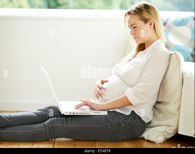 Pregnant woman using laptop computer - Stock Image