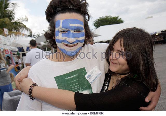 Miami Florida Kendall St. Andrew Greek Orthodox Church Greek Festival boy girl teens couple Greece flag painted - Stock Image
