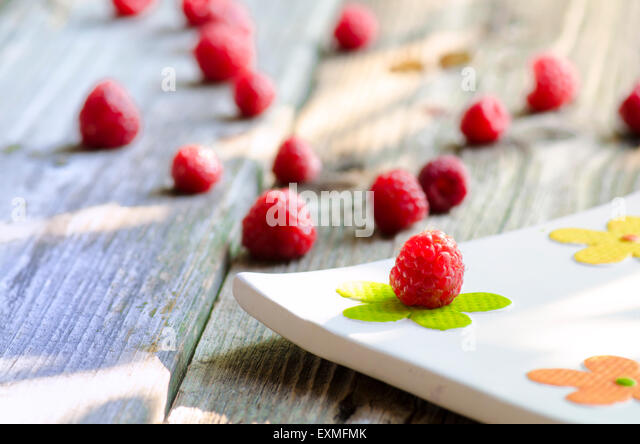 Rasberries on modern white plate isolated on wood background - Stock Image