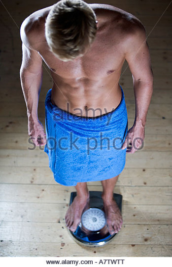 A man wearing a blue towel standing on a set of scales - Stock Image