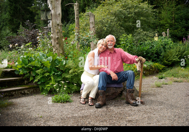 Portrait of senior couple sitting in garden - Stock Image