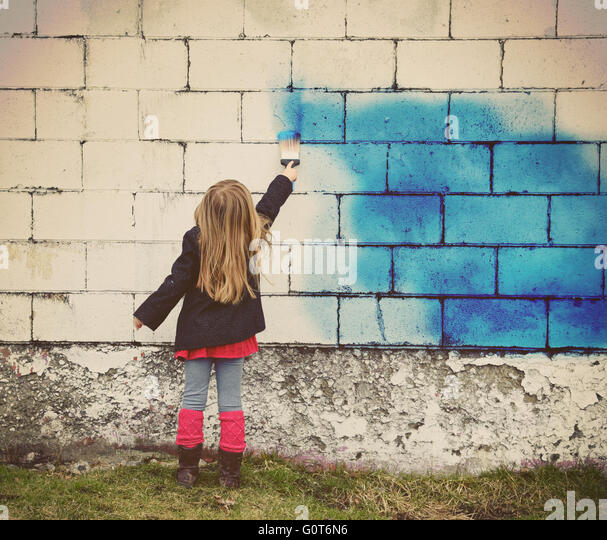 A little child is painting an old white brick wall with blue paint for creative art concept or design idea. - Stock Image