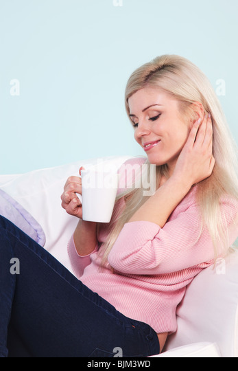 Blond woman sat in an armchair with a mug of tea. - Stock Image