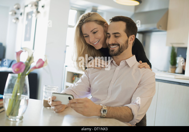 Couple at home looking at pictures on smartphone - Stock Image