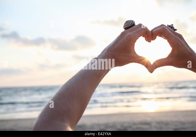 Female hands making heart shape at sunset on beach - Stock Image
