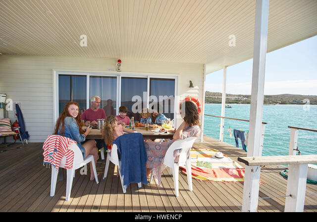 Family gathered at table on houseboat sun deck, Kraalbaai, South Africa - Stock-Bilder