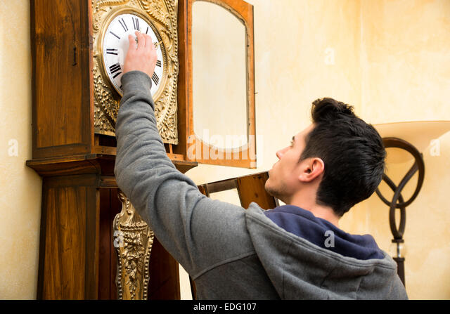 Young man checking a pendulum and winding the mechanism - Stock Image