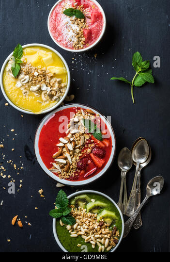 Healthy summer breakfast concept. Colorful fruit smoothie bowls with nuts and oat granola served with mint leaves - Stock Image