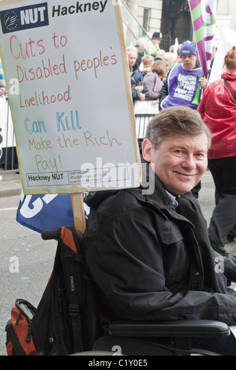 Man in wheel chair 'Cuts to disabled people's Livelihood can Kill Make the Rich Pay ' TUC march Government - Stock Image