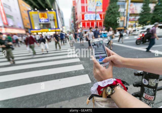 A woman tries to catch a Pokemon character Rattata at Akihabara electronics district on July 25, 2016, Tokyo, Japan. - Stock-Bilder