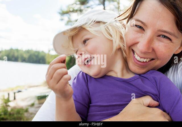 Sweden, Vastergotland, Vattlefjall nature reserve, Mother holding daughter (2-3) - Stock Image