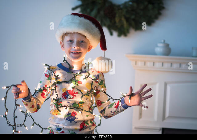 Portrait of boy (6-7) holding christmas lights - Stock Image