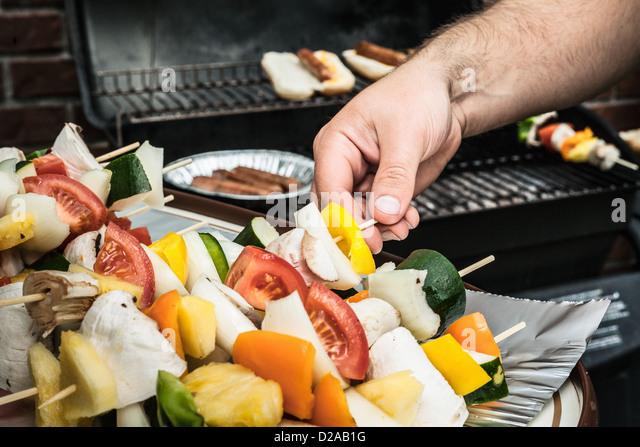 Man grilling vegetable skewers - Stock Image