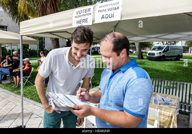 Miami Beach Florida Collins Park voter registration Spanish English Hispanic man survey questionnaire - Stock Image