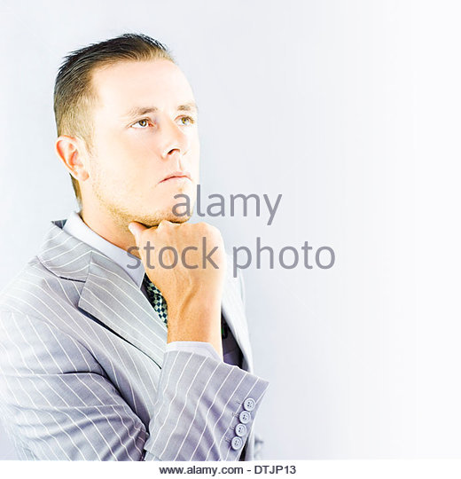 Young businessman looking thoughtful as he conciders his latest decisions - Stock Image