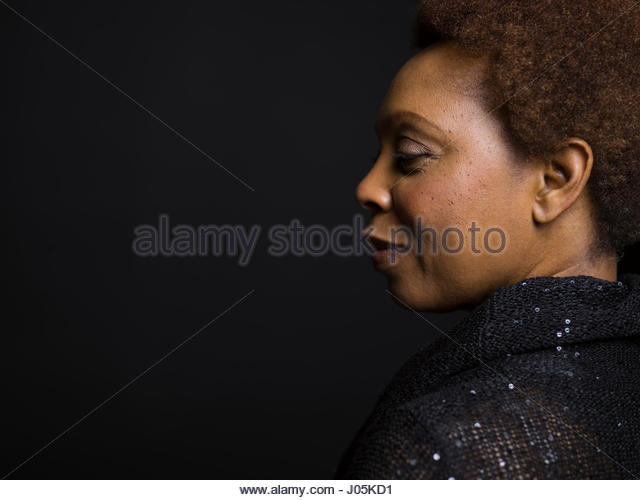Profile portrait confident African American woman looking down against black background - Stock Image