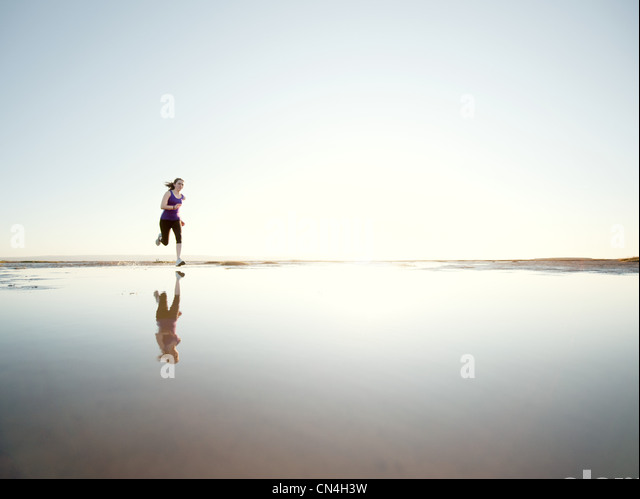 Teenage girl running on water - Stock Image