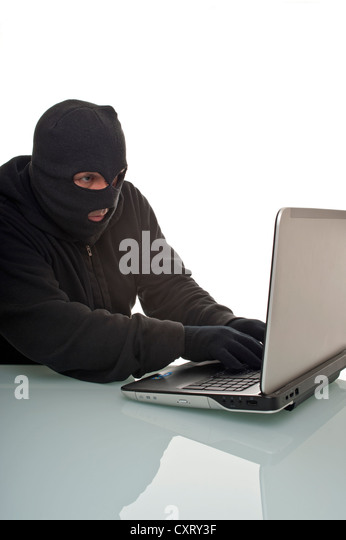 Hacker surfing the internet with a laptop computer, symbolic image for computer hacking, computer or cyber crime, - Stock Image