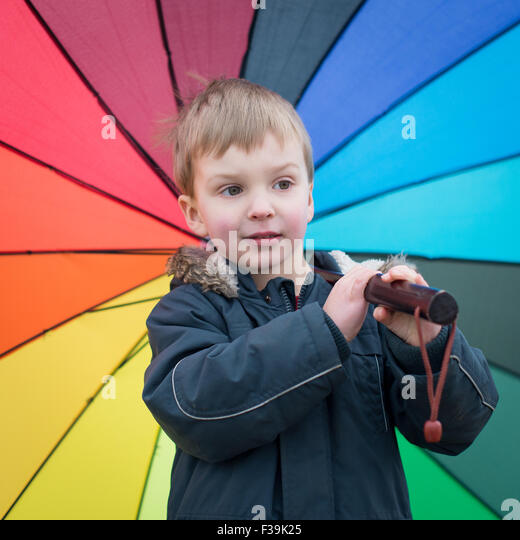 Boy carrying rainbow colored umbrella - Stock Image