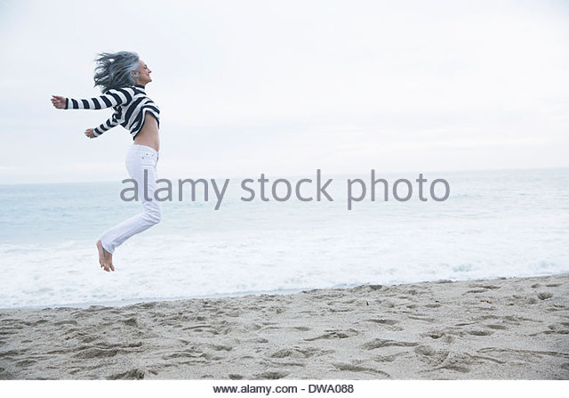 Mature woman jumping mid air on beach, Los Angeles, California, USA - Stock Image