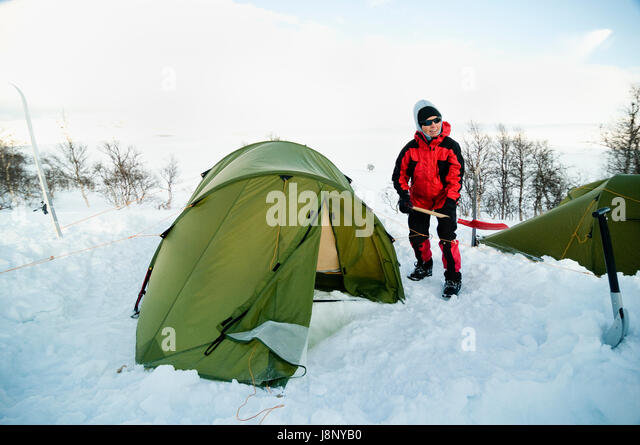 Woman with shovel standing by tent - Stock-Bilder