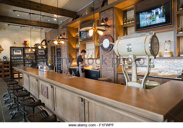 Worker behind bar at distillery - Stock Image