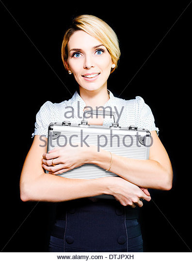 Pretty blonde business woman clutching on tightly to a metal briefcase which she is guarding carefully as it contains - Stock Image