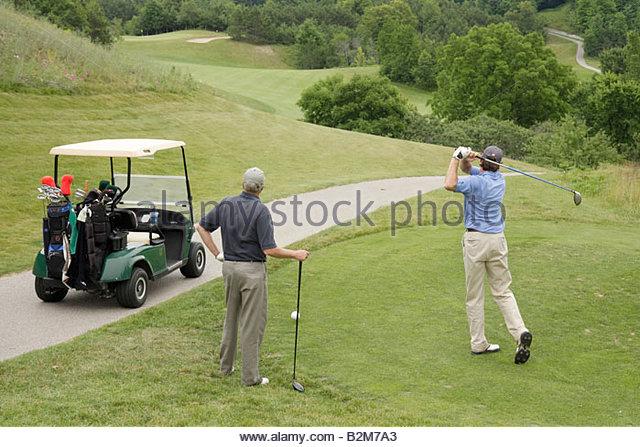 Michigan Traverse City Suttons Bay Leelanau Peninsula Leelanau Club golf course man men cart club swing tee shot - Stock Image