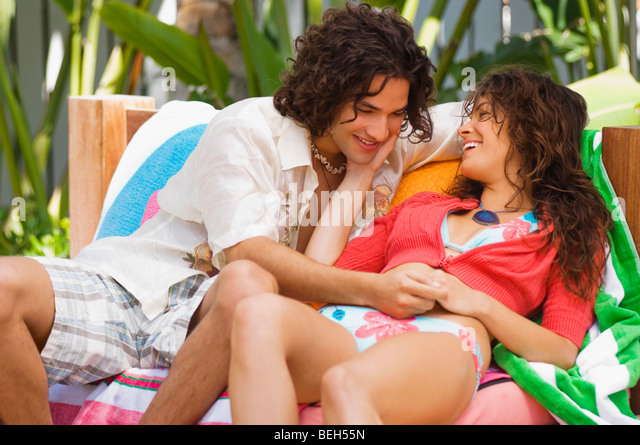 Young couple sitting on a couch and smiling - Stock-Bilder