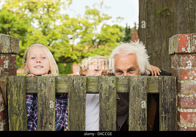 Grandfather and grandchildren peering over wooden gate - Stock Image