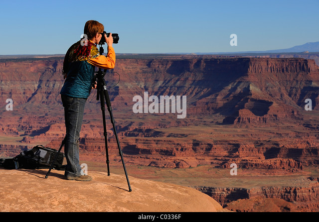 Woman photographer taking a picture with a SLR mounted on a tripod in Canyonlands National Park, Island in the Sky, - Stock Image