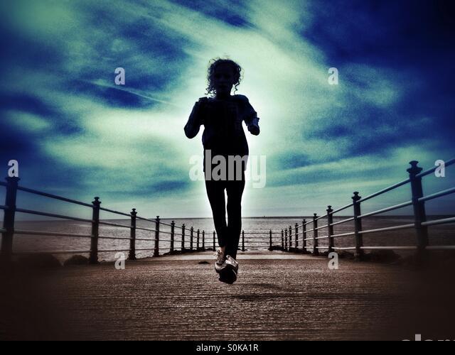 Girl in silhouette running along Stone Jetty in Morecambe - Stock-Bilder