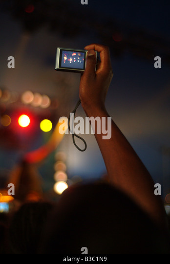 A hand holding up camera to take photo at festival - Stock Image