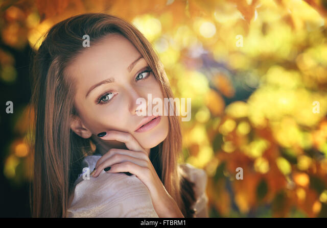 Warm autumn portrait of a young woman . Golden leaves behind - Stock Image