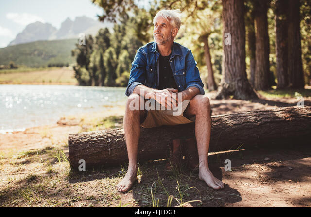 Portrait of a senior man sitting on a log near lake and looking away. Mature man sitting alone on lake. - Stock Image