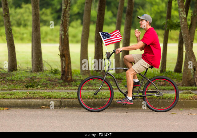A bicyclist rides past with American flag during the Daniel Island ndependence Day parade July 3, 2015 in Charleston, - Stock-Bilder