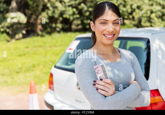 happy learner driver holding her driver's license - Stock Image