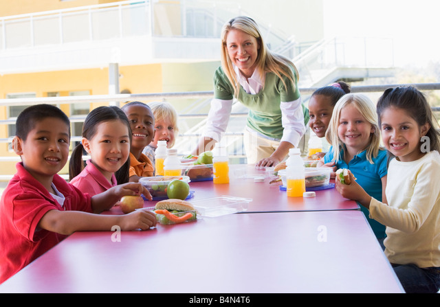 Teacher leaning on table outdoors while students eat lunch (high key) - Stock-Bilder