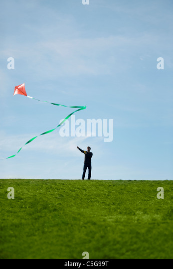 A man flying a red kite - Stock Image