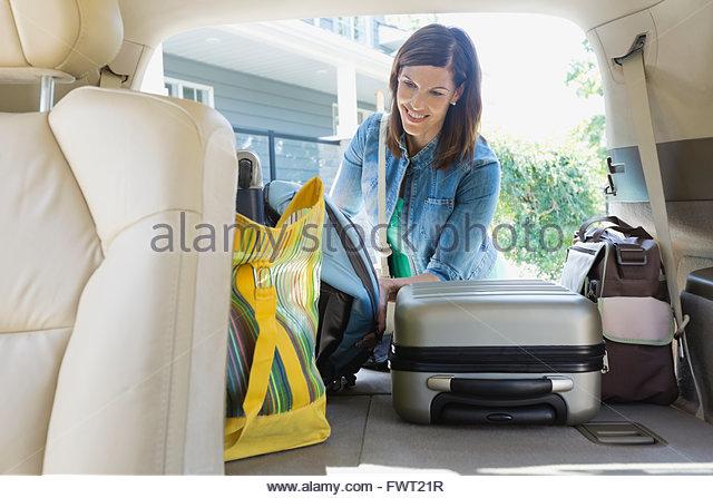 Woman loading luggage into minivan - Stock Image