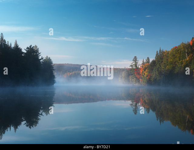 Mist over Smoke lake at dawn. Beautiful fall nature scenery. Algonquin Provincial Park, Ontario, Canada. - Stock-Bilder