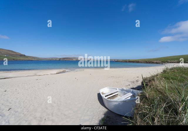 A Boat Abandoned On A Beach Along The Coast; Shetland Scotland - Stock Image