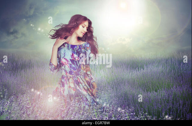 Fantasy. Woman in Enigmatic Meadow over Cloudy Sky - Stock Image