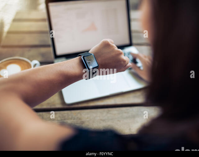 Close up shot of a woman checking time on her smartwatch. Female sitting in cafe with a laptop and cup of coffee. - Stock Image