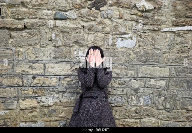 Young woman standing outdoors by stone wall covering eyes - Stock Image