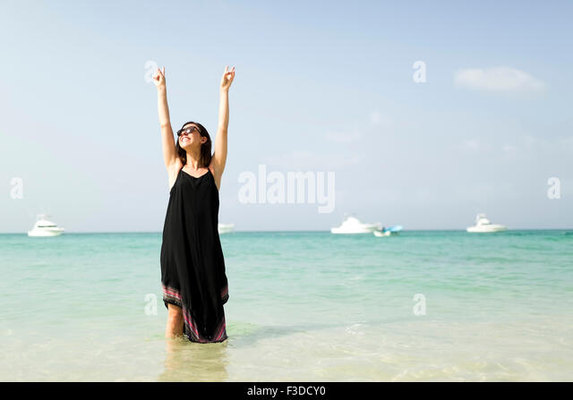Woman with arms raised on beach - Stock Image