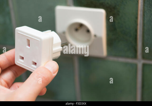 Close Up Of Hand Putting Electric Travel Adapter Into European Socket - Stock-Bilder