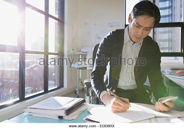 Architect drafting plans in sunny office - Stock-Bilder