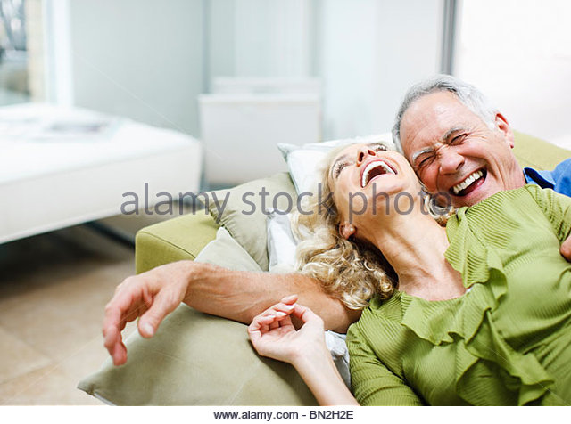 Couple laying on sofa together - Stock Image