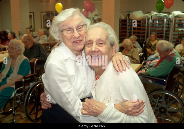 New Jersey Morristown nursing home residents seniors elderly women hug aging wheelchair - Stock Image